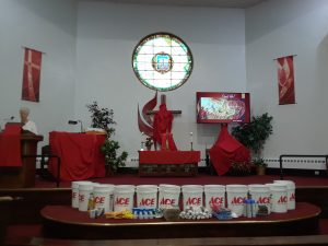Picture of Sanctuary decorated for Pentecost with flood buckets.